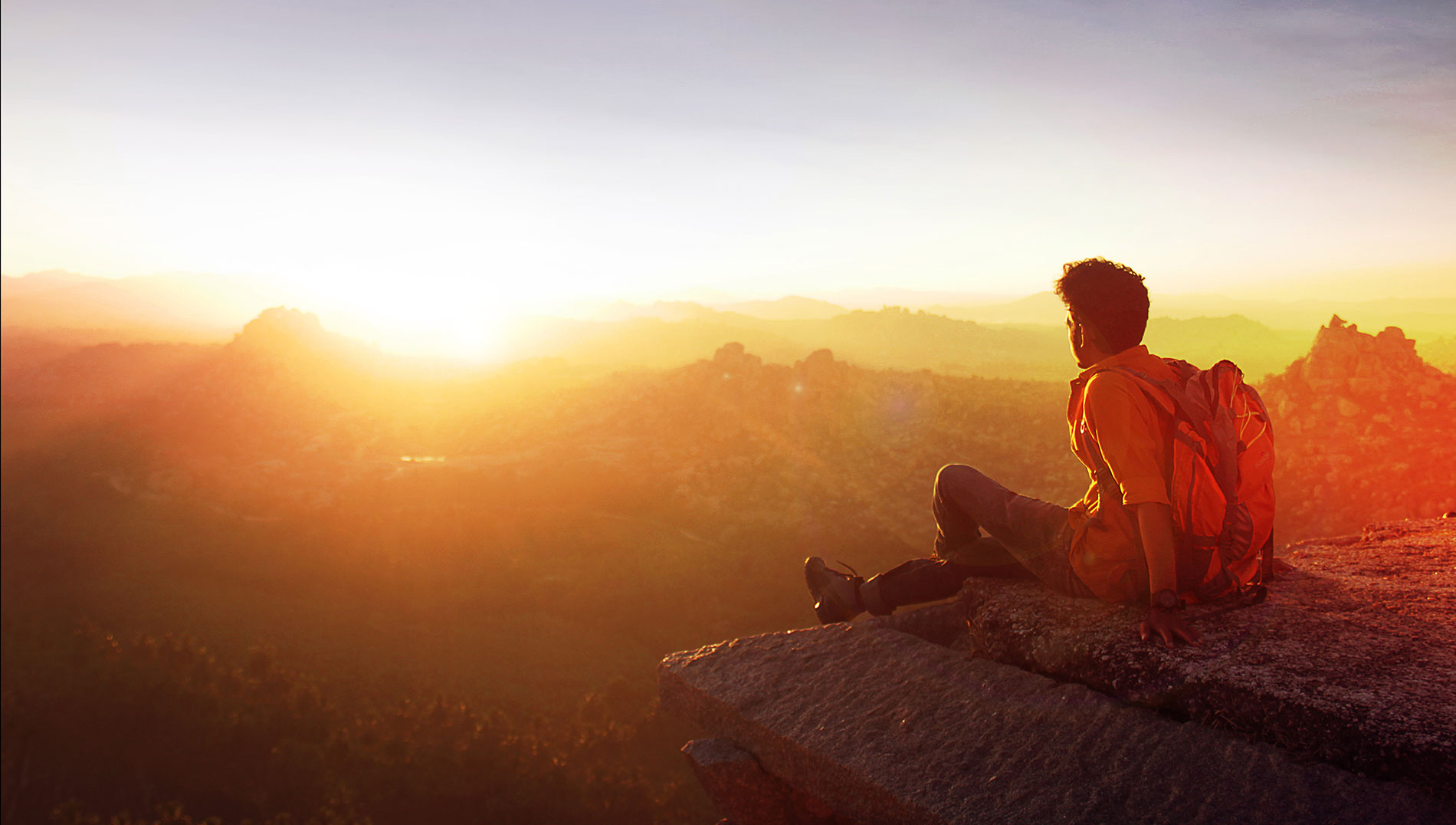 A man sitting on the top of a mountain serenely looking at a beautiful sunrise.