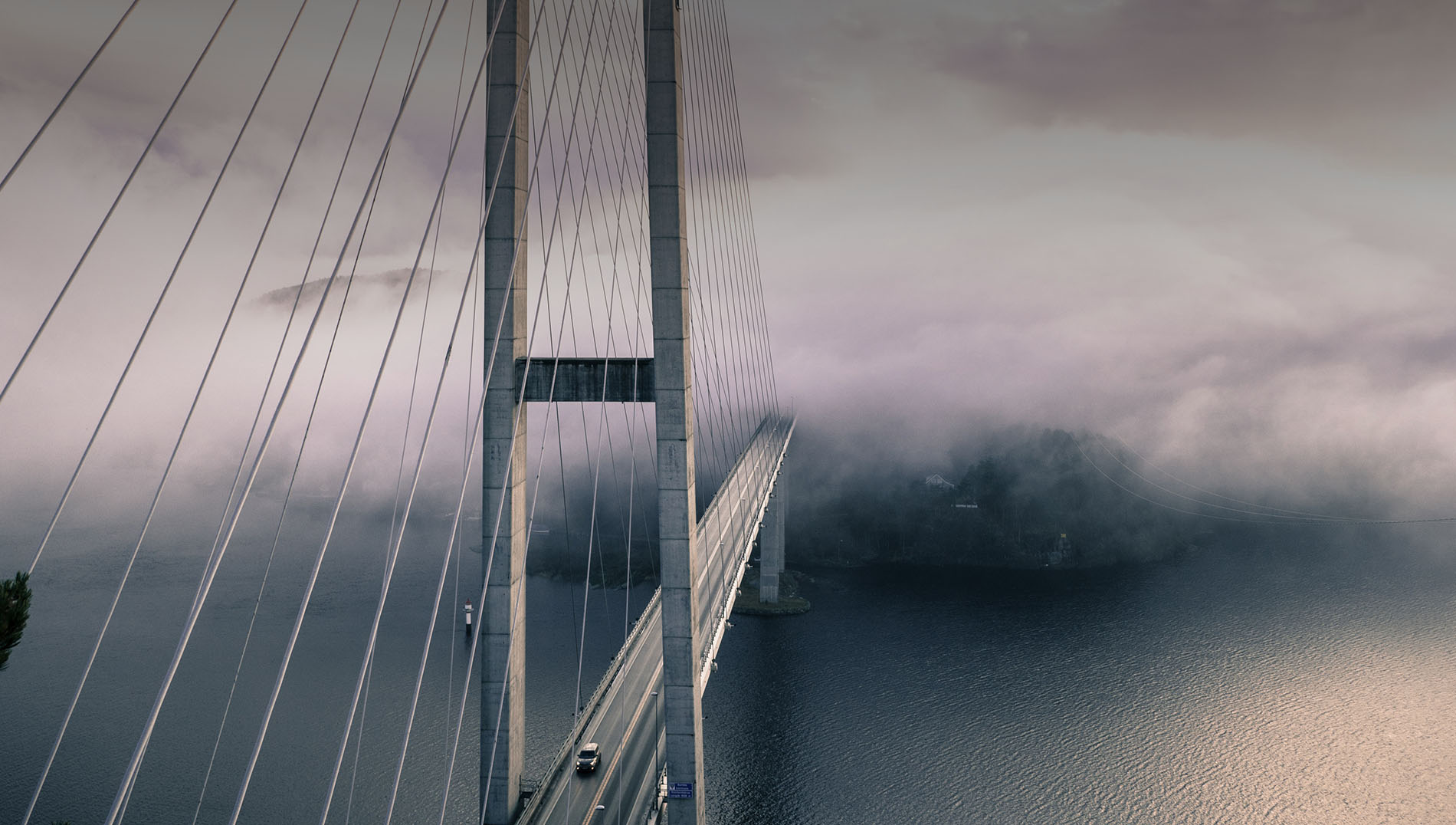 Suspension bridge partly obscured by a thick fog.